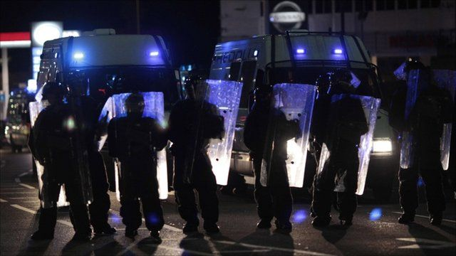 Riot police holding up shields
