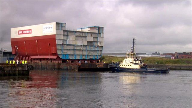 Aircraft carrier hull leaves the BAE shipyard on a barge