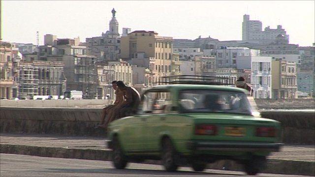A Lada car drives through Havana seaside