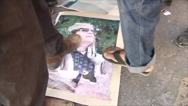 Anti-Gaddafi fighters destroy posters of his image