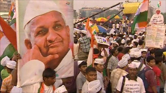 Protesters hold a poster of Hazare