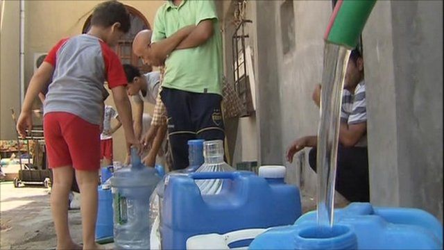 People filling containers with water in Tripoli