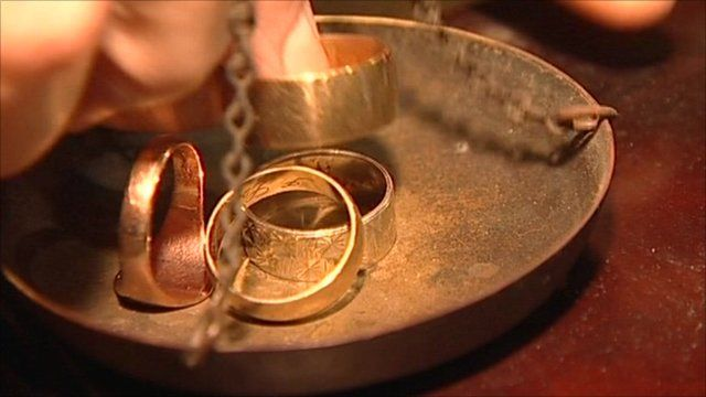Gold rings being put on scales