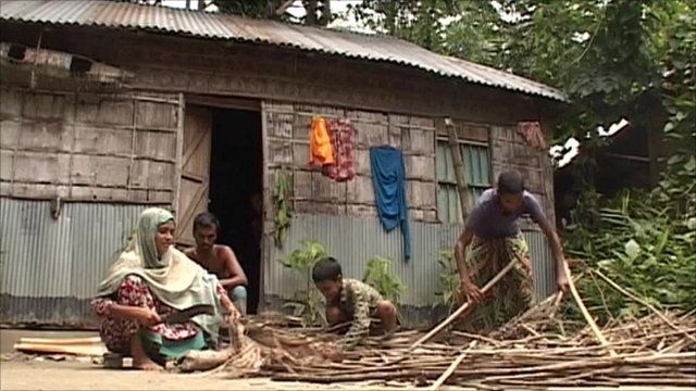 People outside rough house in Doshchura, Indian enclave in Bangladesh