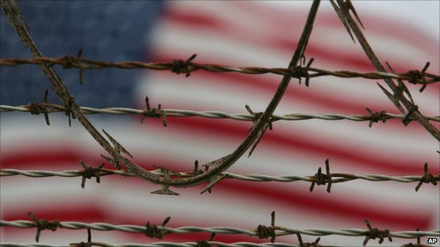 US flag can be seen (blurred) behind barbed wire at Guantanamo Bay