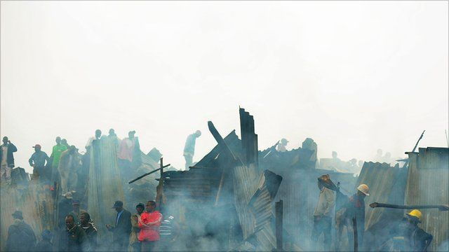Firemen and other people at the site of the pipeline explosion in Kenya's capital, Nairobi