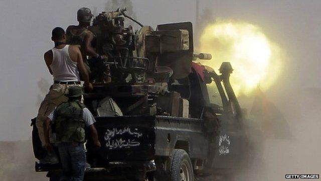 Fighters loyal to Libya's new leaders fire their artillery
