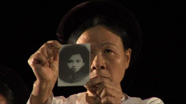 Vietnamese woman shows the picture of a relative who died in the war