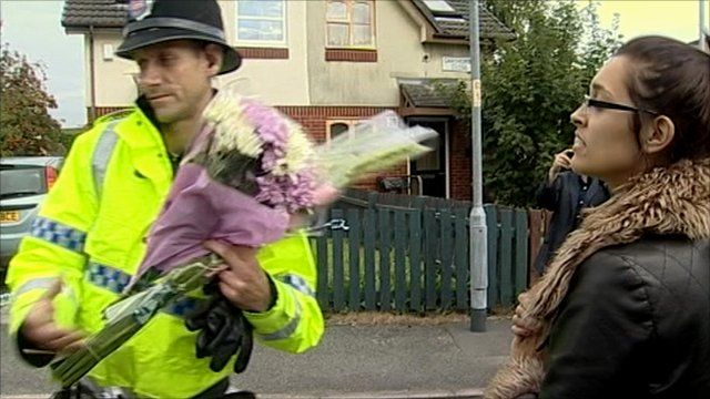 Police officer carrying floral tributes