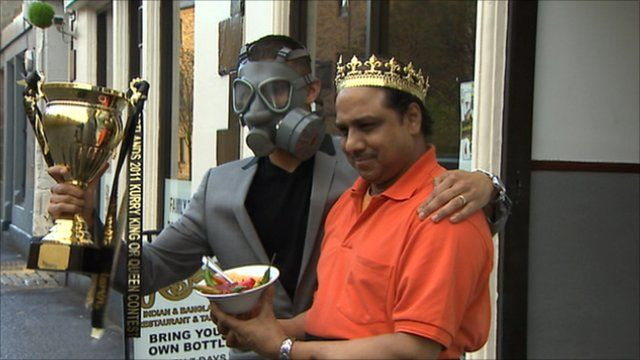 Men with a bowl of curry standing outside the restaurant which held the world's hottest chilli' competition
