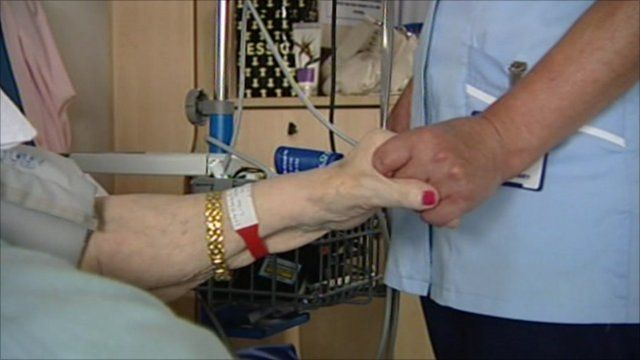 Nurse holds patient's hand