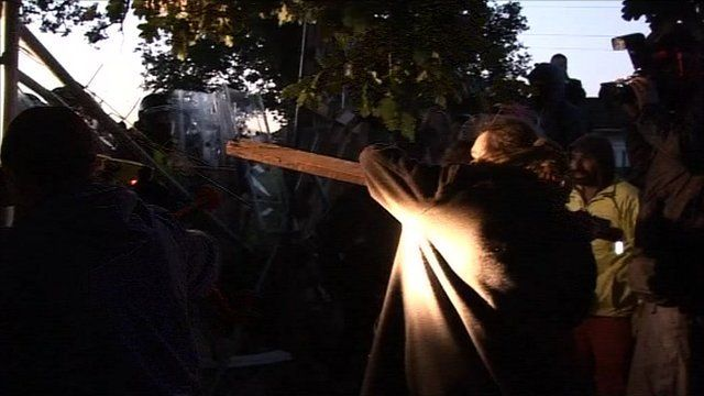 Man holds up plank of wood to police