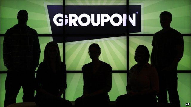 Groupon employees in front of Groupon Logo