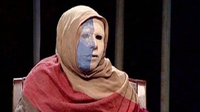 An Afghan woman wearing a mask