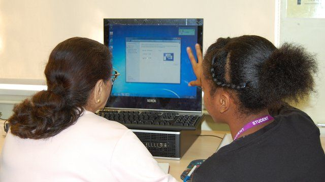 Student teaching an older woman to use the internet