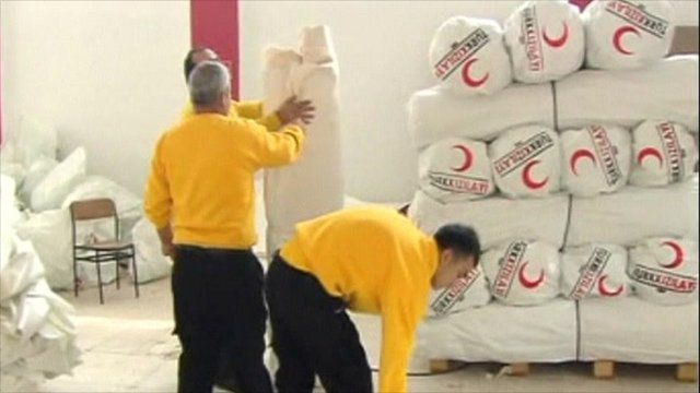 Red Crescent workers preparing tents and blankets for distribution