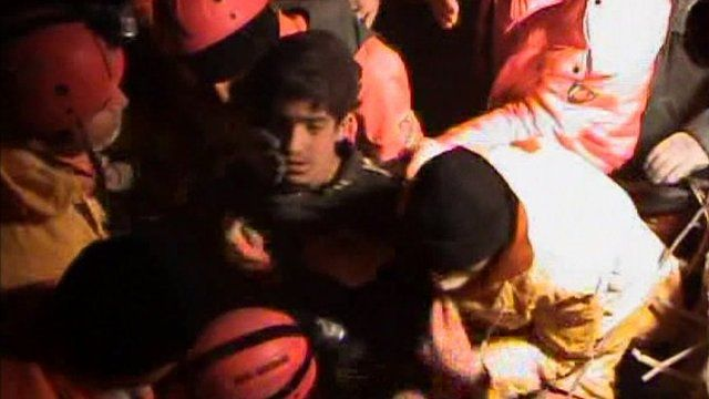 Teenage boy being carried by rescue workers