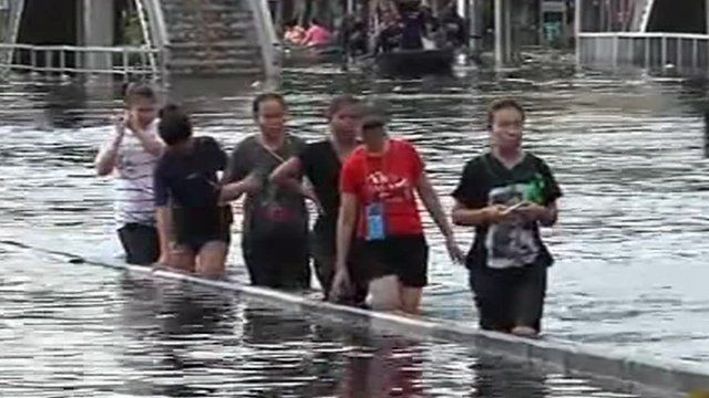 People wade through water in Thailand