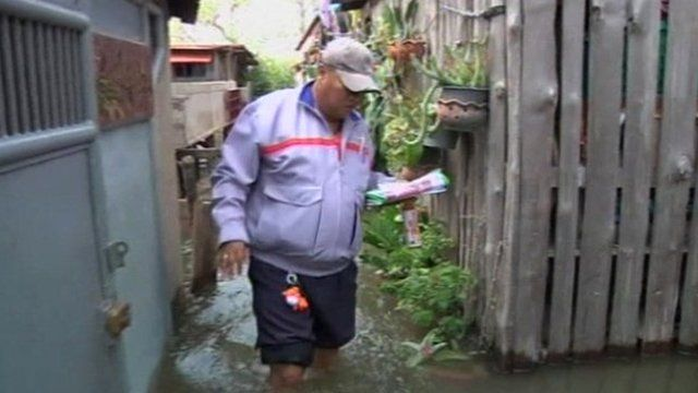 Postman Somyod Somsamai in flooded area of Bangkok