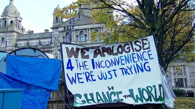 "Protesters sign reading ""We Apologise 4 the inconvenience, we're just trying to change the world"""