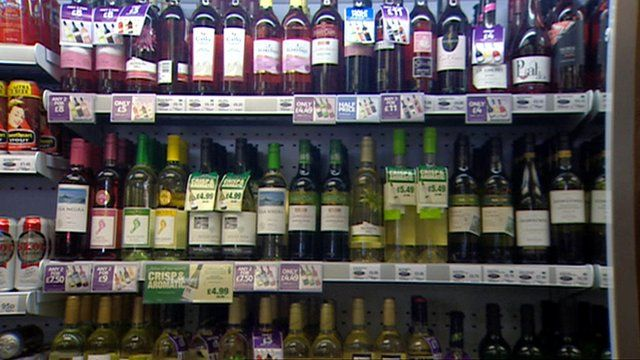 Bottles of wine and cans of beer on a supermarket shelf