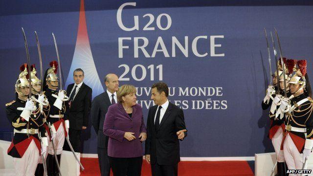 French President Nicolas Sarkozy (R) welcomes German Chancellor Angela Merkel