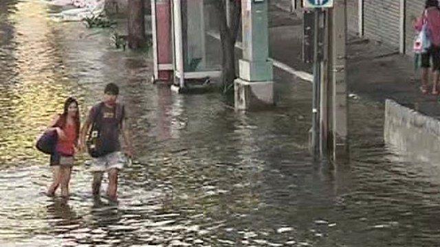 Couple walking through knee-deep waster in Bangkok street
