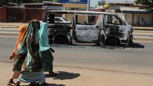 Young girls walk past a vehicle burnt in Damaturu, Nigeria