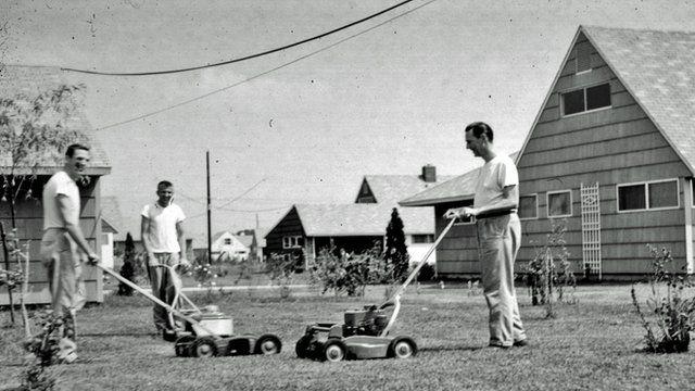 Men pushing lawn-mowers in 1950's Levittown