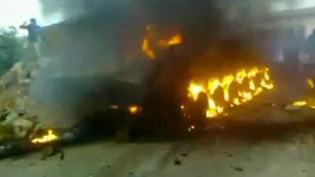 A Syrian Army APC burns in the city of Deraa