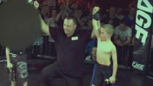 Boy in cage fighting ring with referee