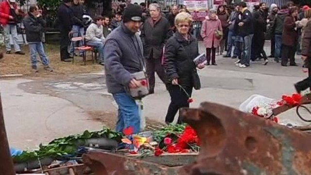 People lay flowers at memorial