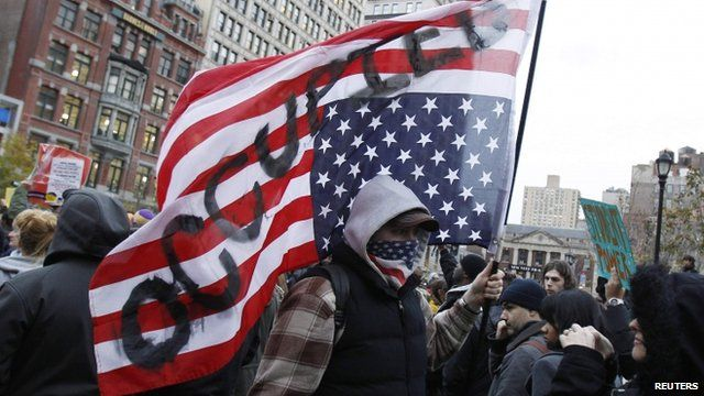 "Occupy Wall Street protester carrying upside down US flag with ""occupied"" written on it"