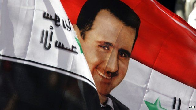 A Syrian flag with an image of President Bashar al-Assad