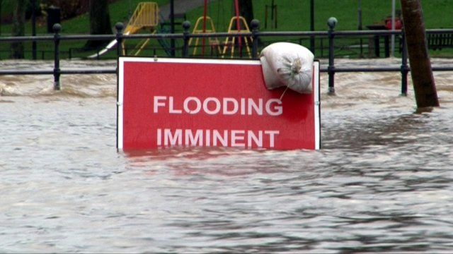 'Flooding imminent' sign surrounded by flood water