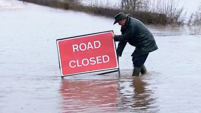 A man with a 'Road closed' sign in flood waters