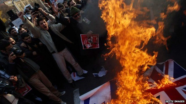 Protesters set fire to the British and Israeli flags outside the British embassy in Tehran