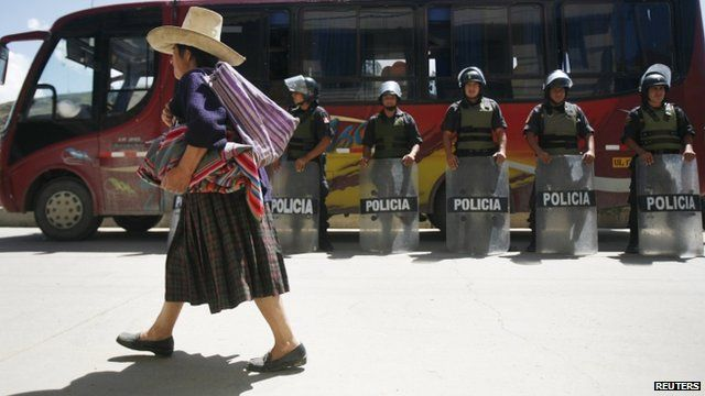 An Andean woman walks next to police officers during the second day of strike against the proposed mine