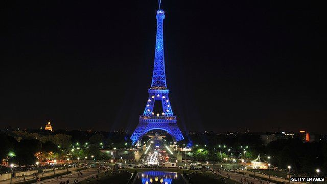 The Eiffel Tower illuminated in blue with gold stars, representing the EU flag