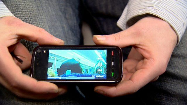 Man holding a mobile showing video footage