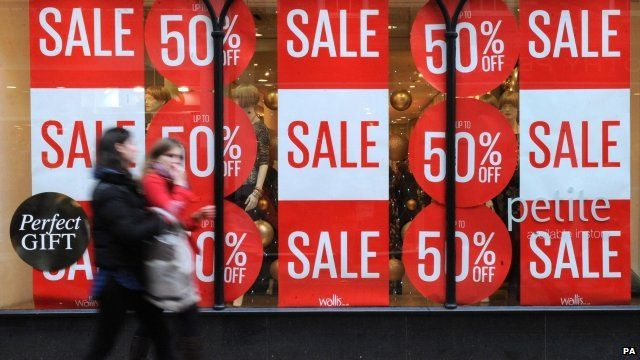 Shoppers outside store with sale posters in window