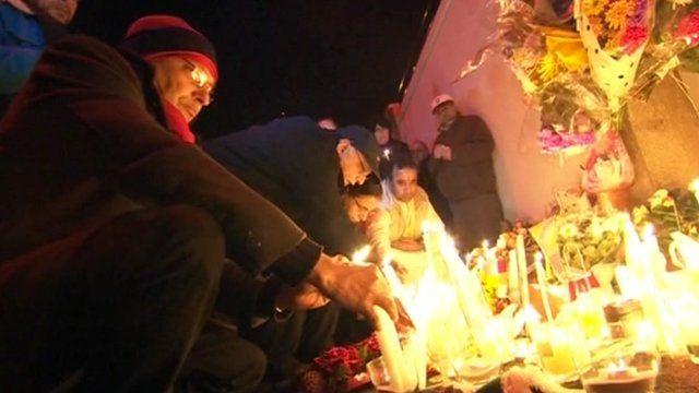 Man placing candle at scene of Anuj Bidve's death