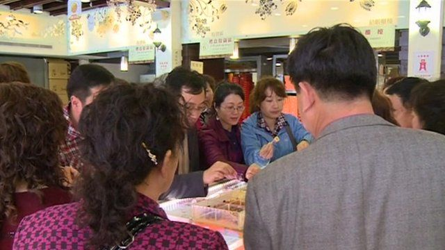 Chinese tourists sample Taiwan's best known snacks at a souvenir shop in the capital Taipei