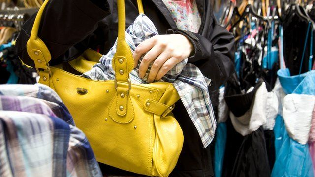 Woman stealing a shirt in a shop