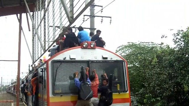 Commuters in Indonesia sitting on the roof of a train