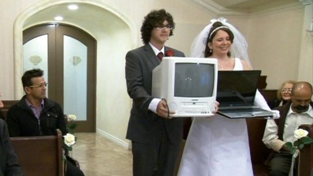 """Staged """"wedding"""" between man carrying a TV and a woman carrying a laptop."""