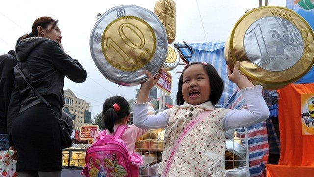A girl holds up cushions shaped as euro and Hong Kong coins at the Chinese New Year flower market in Hong Kong