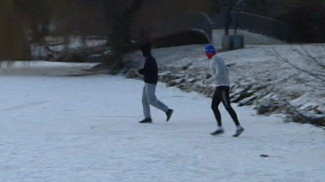 People walking across a frozen lake