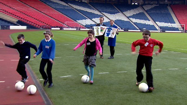 School children kick footballs in Hampden Park