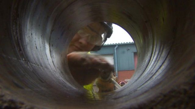 Man looking through hole drilled in concrete